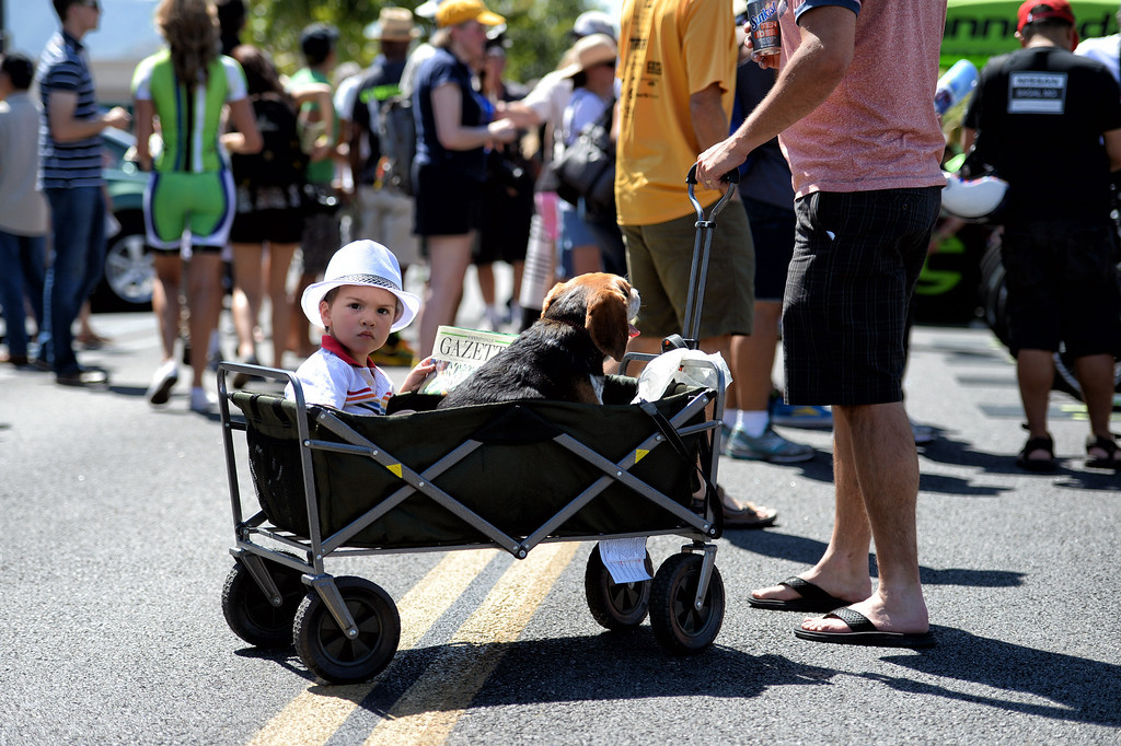 . Finley Kaukola, 3-years-old, and dog Buddy get pull by dad Danny as they check out the festivities in Newhall before the start of stage 6 of the Amgen Tour of California bicycle race. (Photo by Hans Gutknecht/Los Angeles Daily News)