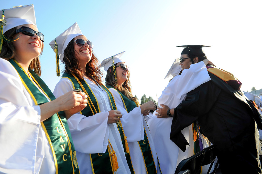 . Assistant professor of nursing Trig Nuyda, right, hugs nursing graduates at the Los Angeles Valley College graduation, Tuesday, June 10, 2014. (Photo by Michael Owen Baker/Los Angeles Daily News)