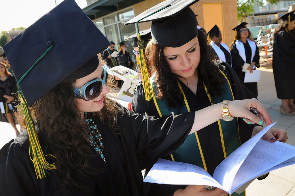 . Sara Avetisyan, left, and Luiza Chelokyan look through the program for their names before the Los Angeles Valley College graduation, Tuesday, June 10, 2014. (Photo by Michael Owen Baker/Los Angeles Daily News)