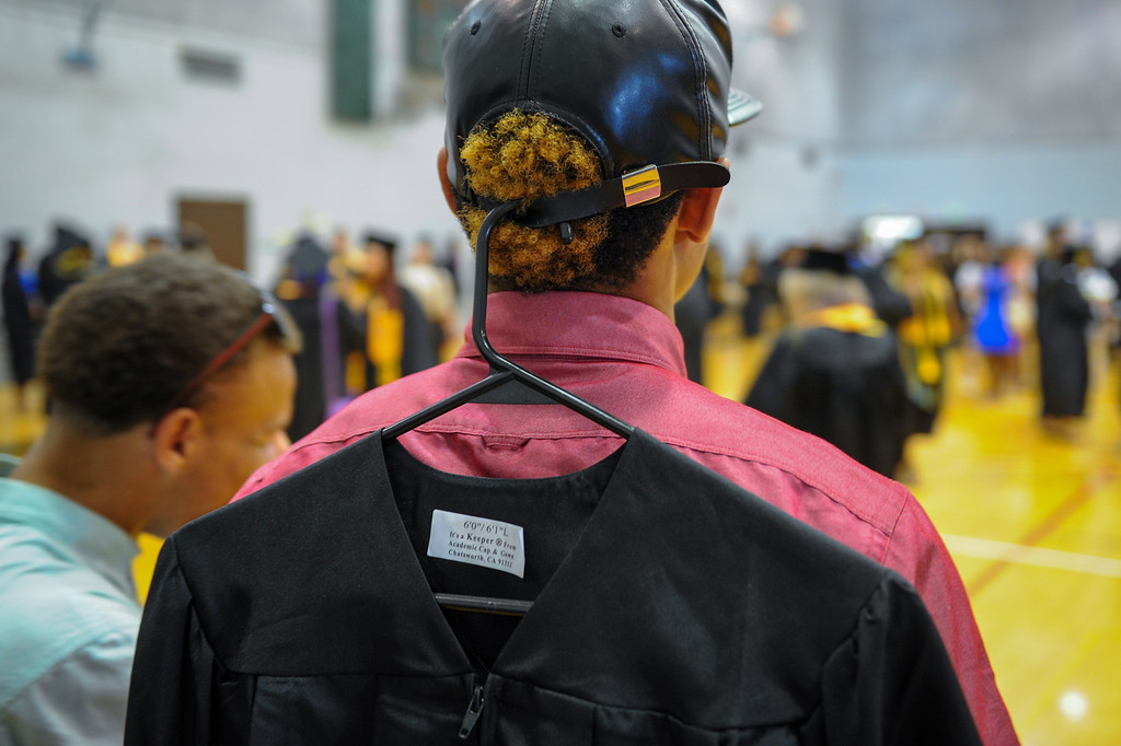 . Jeremi Ross hangs his gown from the back of his cap before the Valley College graduation, Tuesday, June 10, 2014. (Photo by Michael Owen Baker/Los Angeles Daily News)