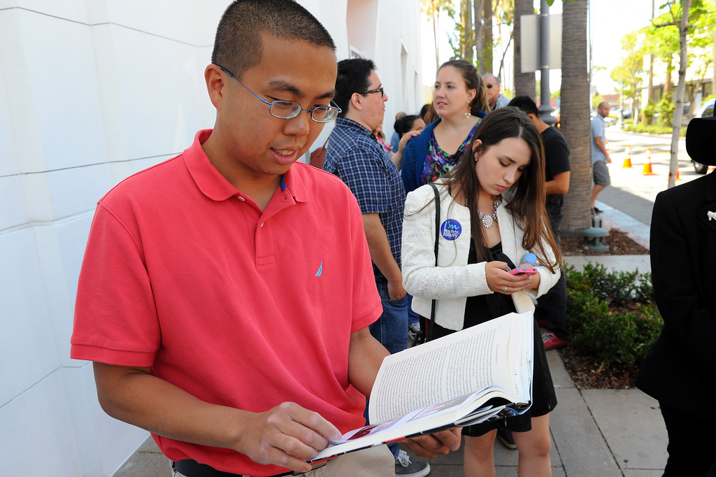 ". Alvin Leung looks through Hillary Rodham Clinton\'s book ""Hard Choices\"" while waiting in line four hours for Clinton\'s book signing at Barnes & Noble at The Grove, Thursday, June 19, 2014. (Photo by Michael Owen Baker/Los Angeles Daily News)"