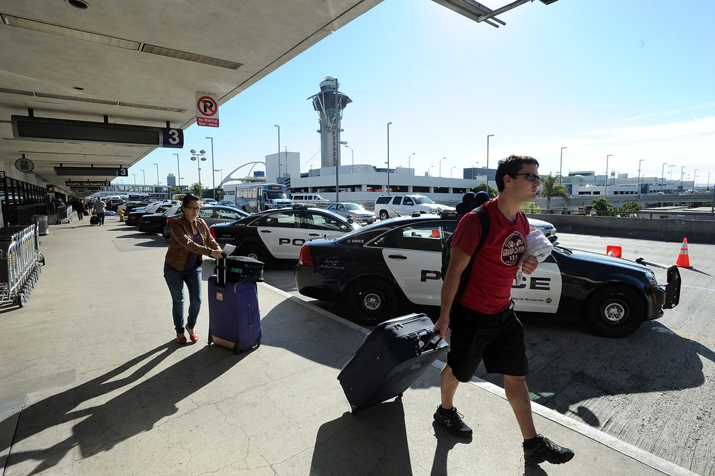 . Travelers pass a line of police cars the day after a gunman entered terminal 3 at Los Angeles International Airport where he killed a TSA agent and wounded several others. Los Angeles, CA. 11/2/2013. photo by (John McCoy/Los Angeles Daily News)