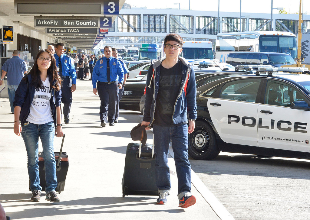 . Travelers walk past police officers the day after a gunman entered terminal 3 at Los Angeles International Airport where he killed a TSA agent and wounded several others. Los Angeles, CA. 11/2/2013. photo by (John McCoy/Los Angeles Daily News)