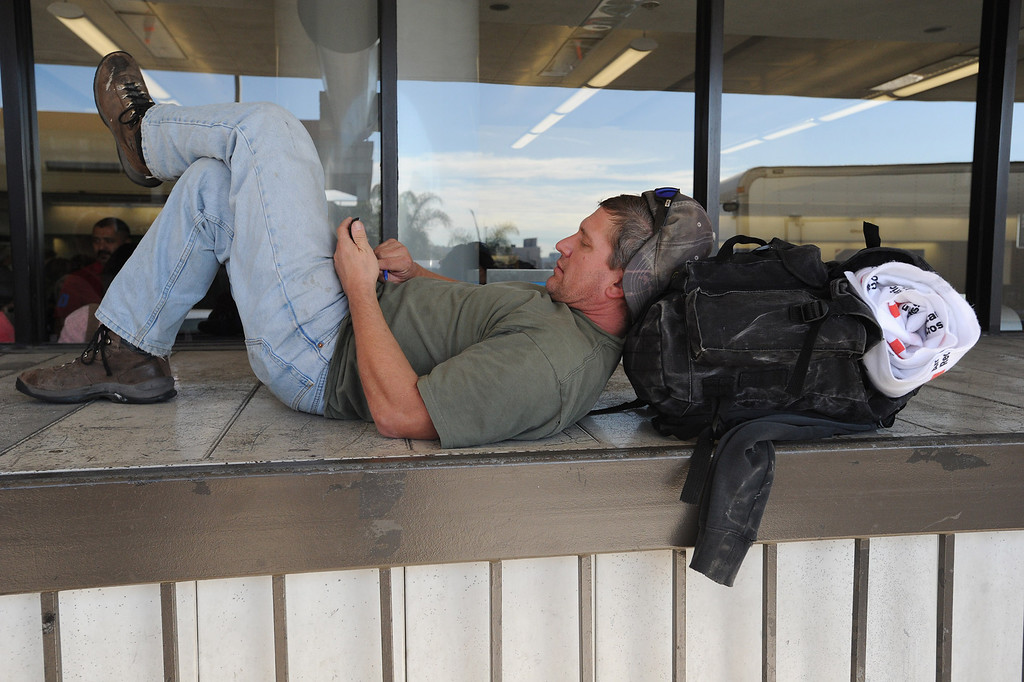 . James Rusk from Fort Collins, Colorado has a red cross blanket in his bag as he sits outside Terminal 3 at LAX.  Friday morning a gunman entered the terminal 3 at Los Angeles International Airport and killed a TSA agent and wounded several others. Los Angeles, CA. 11/2/2013. photo by (John McCoy/Los Angeles Daily News)