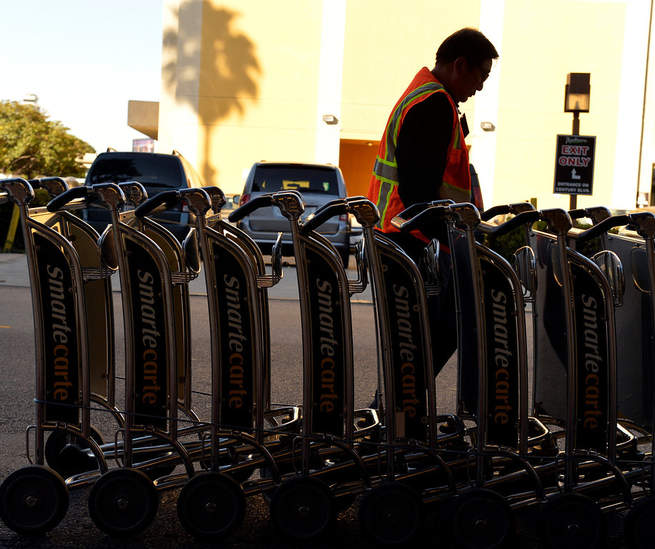 . Jone Ly collects carts around the hotels of LAX after a shooting the day before in Los Angeles, CA. Saturday November 2, 2013. (Thomas R. Cordova/Press-Telegram/Daily Breeze)