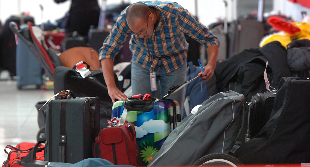 . Passengers luggage fills a space as workers go through it in terminal 3 at LAX as it reopens after a shooting the day before in Los Angeles, CA. Saturday November 2, 2013. (Thomas R. Cordova/Press-Telegram/Daily Breeze)