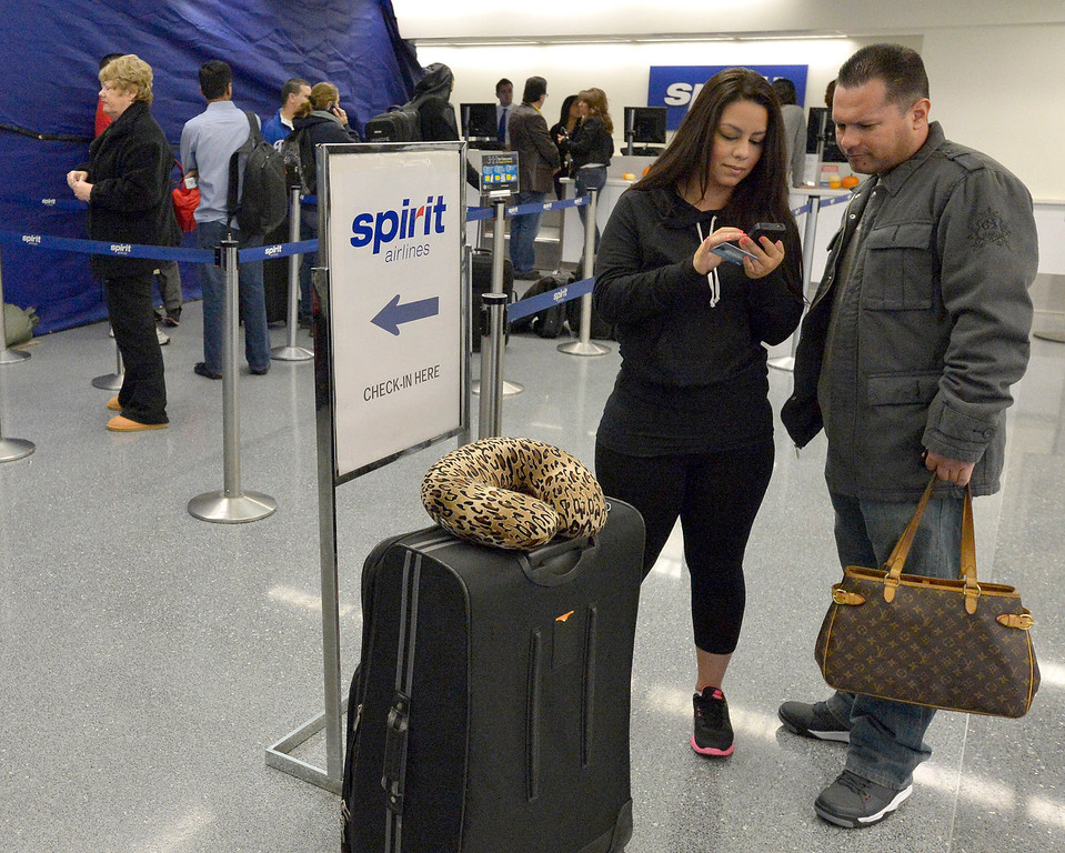 . Ceci Hernandez and her husband Steve Lopez make arrangements for another flight after theirs was canceled. The pair was traveling the day after a gunman entered terminal 3 at Los Angeles International Airport where he killed a TSA agent and wounded several others. Los Angeles, CA. 11/2/2013. photo by (John McCoy/Los Angeles Daily News)