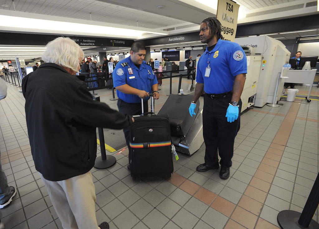 . TSA agents help passengers with baggage the day after a gunman entered terminal 3 at Los Angeles International Airport where he killed a TSA agent and wounded several others. Los Angeles, CA. 11/2/2013. photo by (John McCoy/Los Angeles Daily News)
