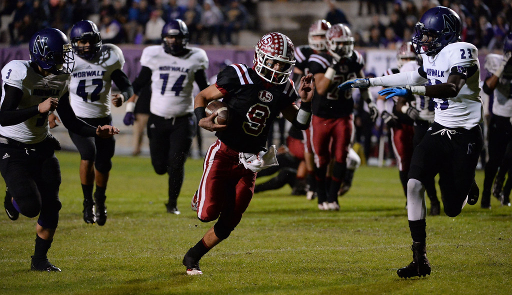 . La Serna quarterback Frankie Palmer (9) runs for a touchdown past Norwalk\'s Dante Foster (23) in the first half of a CIF-SS Southeast Division championship football game at Cal State Fullerton stadium in Fullerton, Calif., on Saturday, Dec. 7, 2013. 