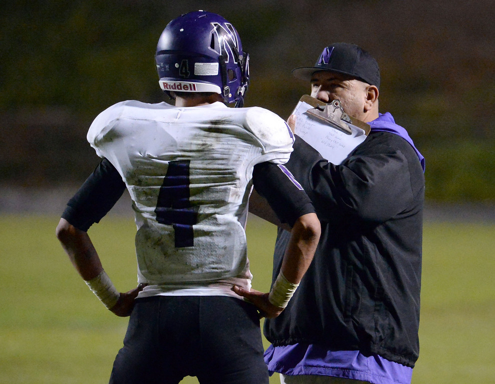 . Norwalk head coach Jesse Ceniceros talks with Jacob Carr (4) in the first half of a CIF-SS Southeast Division championship football game at Cal State Fullerton stadium in Fullerton, Calif., on Saturday, Dec. 7, 2013. 