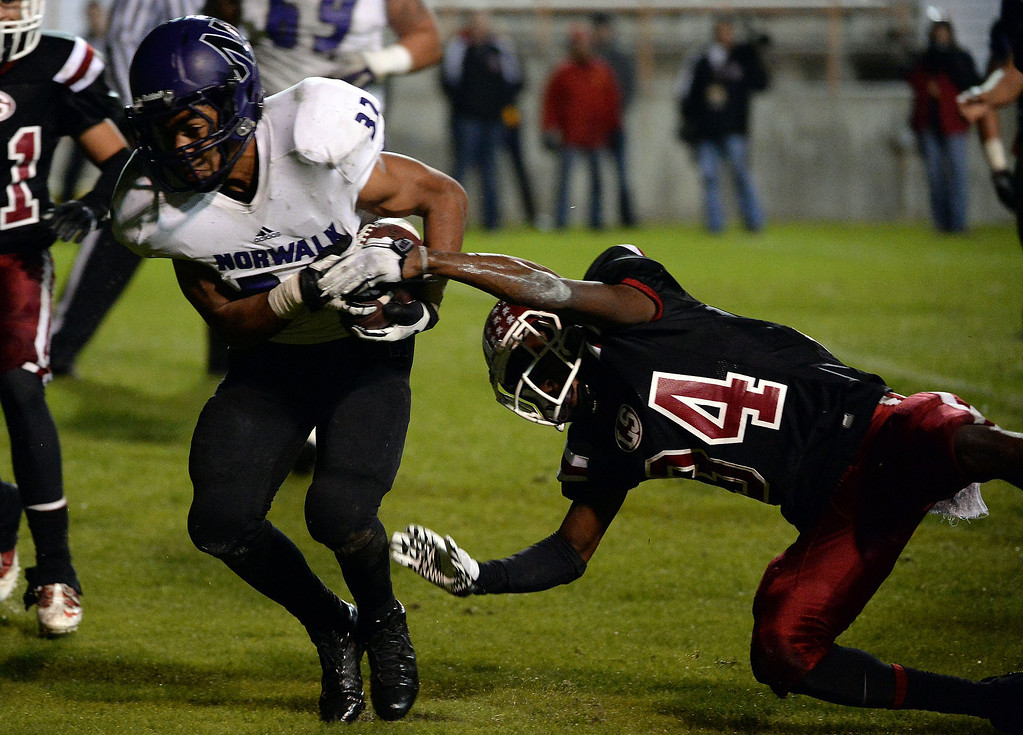 . Norwalk\'s Christopher Walker (32) ru ns past La Serna\'s Jalen Thompson (34) for the two point conversion in the first half of a CIF-SS Southeast Division championship football game at Cal State Fullerton stadium in Fullerton, Calif., on Saturday, Dec. 7, 2013. 