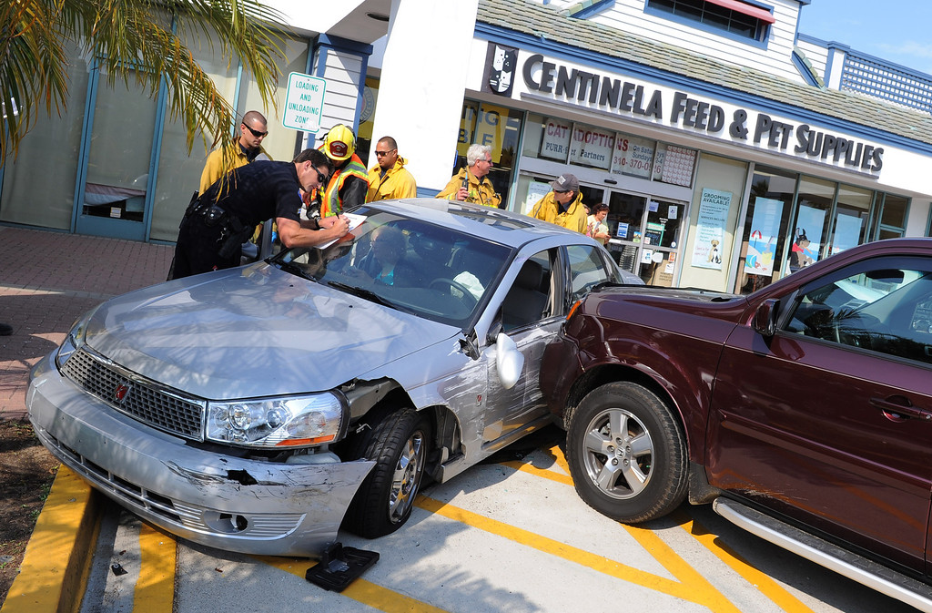 . An out-of-control vehicle (at left) in the Redondo Shores shopping center careened through the display windows of a clothing store and continued on, hitting two parked cars. 4:30 pm incident. Photo by Brad Graverson 7-1-13