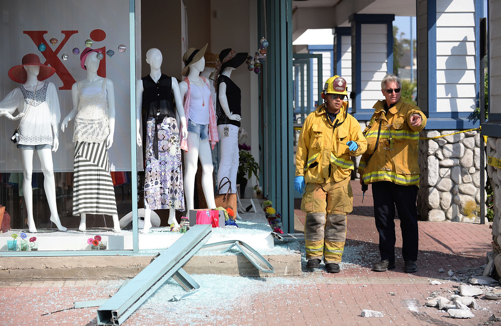 . An out-of-control vehicle in the Redondo Shores shopping center careened through the display windows of the Xi clothing store (at left) and continued on, hitting two parked cars. 4:30 pm incident. Photo by Brad Graverson 7-1-13