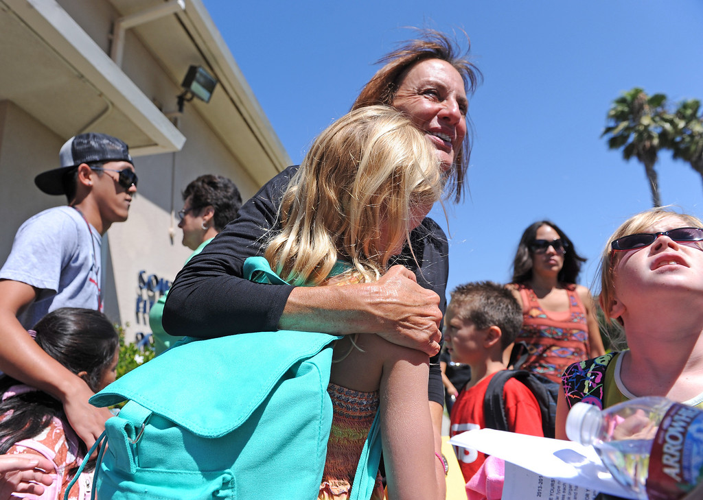 . Second grade teaches Kate Stewart gives kids a hug goodbye till tomorrow as students leave South Shores Performing Arts Magnet School in San Pedro after the first day of classes.   Photo by Brad Graverson 8-13-13
