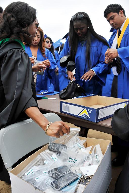 . LONG BEACH- 6/12/2013 - (Mark Savage) Graduating students turn in their phones before the ceremony begins. Jordan High School commencement at Veterans Memorial Stadium.