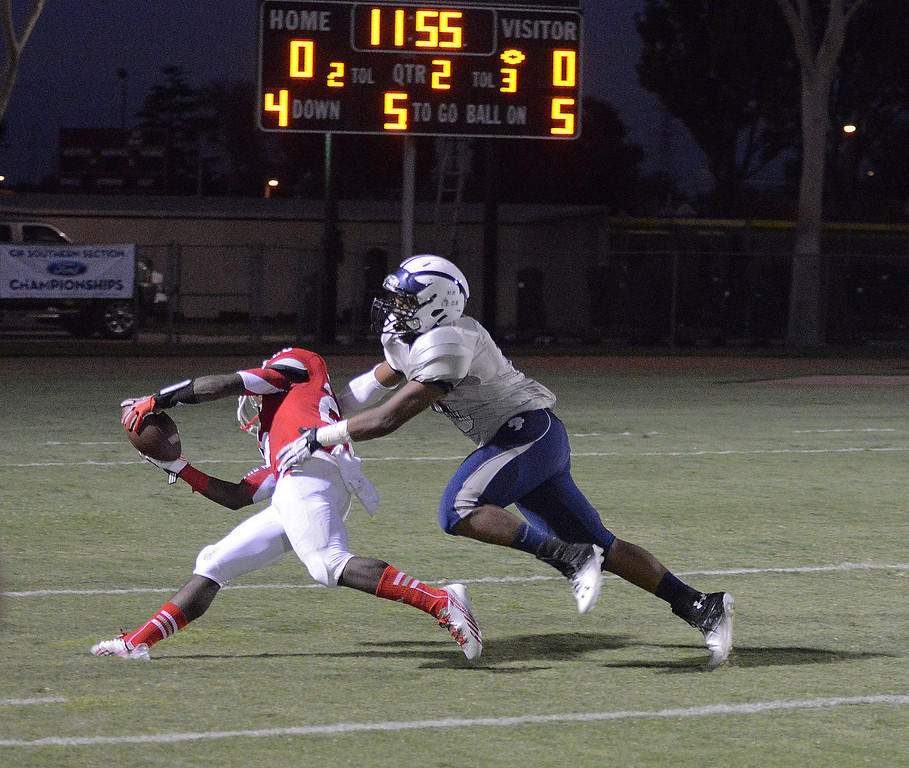 . Local rivals Lakewood and Mayfair play at Bellflower High School for the Milk Bucket Trophy in Bellflower, CA. on September 13, 2013. Jason Floyd scores a touchdown for Lakewood over Mayfair\'s Vaughn Johnson. (Photo by Sean Hiller/Press Telegram)