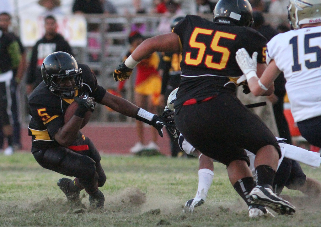 . August 30, 2013. Dominguez\'s Keith Hariston (5), left, changes direction behind the block of Ioane Niupulusu (55), center, while St. John Bosco\'s Brett Baldwin (15), right, looks to make the stop during Friday nights game at Dominguez High School in Compton, California. (Mark Dustin/For the Long Beach Press-Telegram)