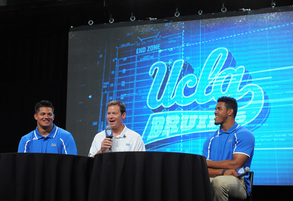 . UCLA Coach Jim Mora with players Xavier Su\'a Filo (OL) left, and Anthony Barr (LB) right. Pac12 media Day at Sony Studios.  Photo by Brad Graverson 7-26-13
