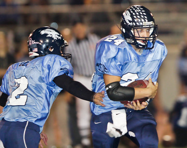 The Falcons' Kyle Cota (2) hands the ball to Harry Pessy (24) quarterback during a football game between the Crescenta Valley High School Falcons and the visiting Arcadia High School Apaches in Glendale, CA on November 12, 2009.  (STAR-NEWS/Correspondent photo by David Thomas/SPORTS)