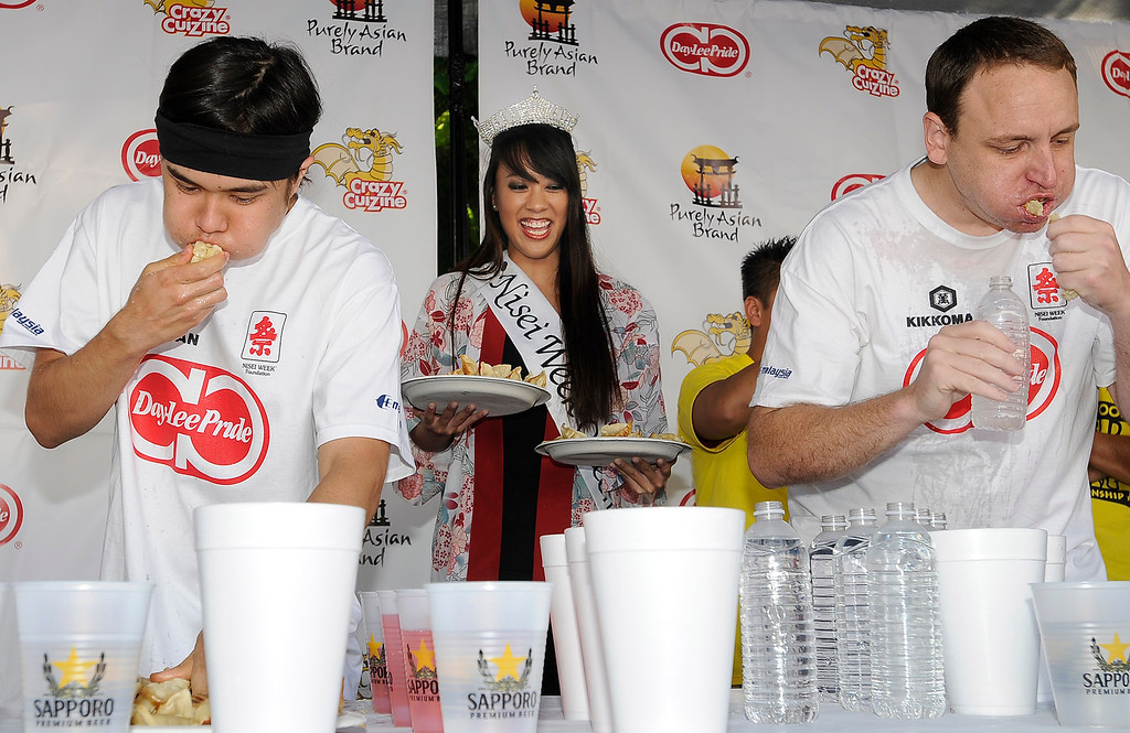 . (l-r) Matt Stonie gets served more Gzoya by Lauren Iwata while Joey Chestnut powers down the pot stickers. The World Gyoza Eating Contest is taking place as part of the annual Nisei Week Foundation festival. Matt Stonie of San Jose ended up setting a new world record by eating 268 pot stickers, edging out last years winner Joey Chestnut who ate 251. Los Angeles, CA. 8/17/2013(John McCoy/LA Daily News)