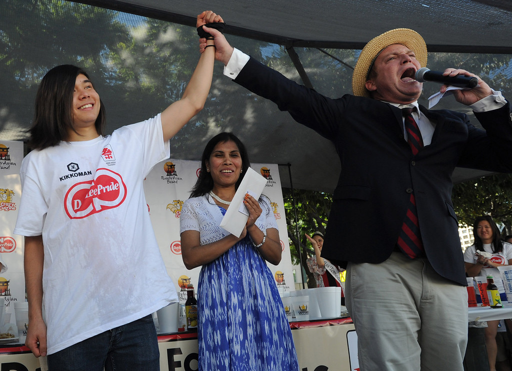 . Matt Stonie has his hand raised in victory by Master of Ceremonies Sam Barclay while Malaysia Airlines sponsor Israt Akhter looks on. The World Gyoza Eating Contest is taking place as part of the annual Nisei Week Foundation festival. Matt Stonie of San Jose ended up setting a new world record by eating 268 pot stickers, edging out last years winner Joey Chestnut who ate 251. Los Angeles, CA. 8/17/2013(John McCoy/LA Daily News)