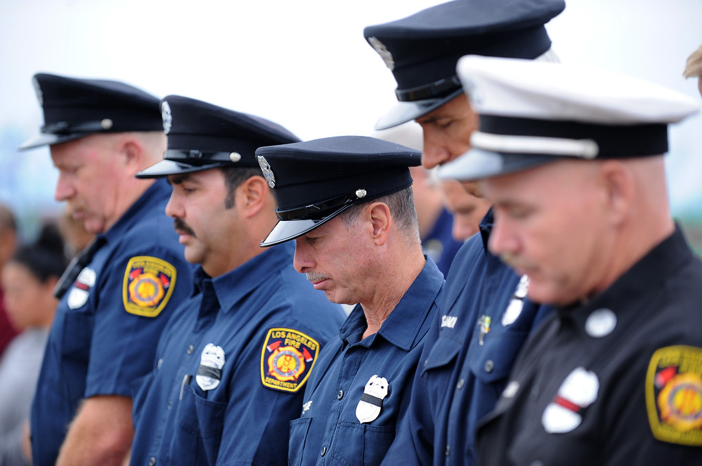 . Firefighter Ray Gallegos, center, with fellow firemen from Station 112, San Pedro during moment of silence. Observance event to honor 9/11 first responders aboard the USS Iowa in San Pedro. (Wed. Sept 11, 2013 Photo by Brad Graverson/The Daily Breeze