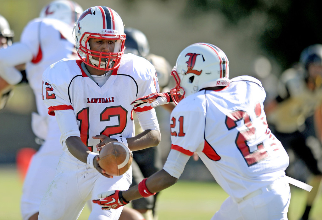 . Lawndale\'s quarterback Chris Murray hands off to Luke Megginson (21) in Friday afternoon\'s high school football game in Rolling Hills Estates in CA. on September 27, 2013. (Photo by Sean Hiller/Daily Breeze)