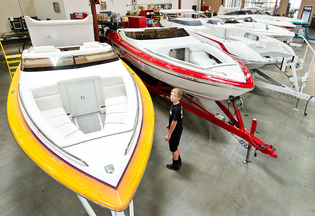 . Bradon Haskell, 13, gives a tour of the boats on display at Hallett Boats dealership in Irwindale on Tuesday, June 25, 2013. Southland boaters are gearing up for the summer season, and in California that�s big business. But companies that sell boats and boating supplies say things are not nearly what they used to be before the recession. (SGVN/Staff photo by Watchara Phomicinda)