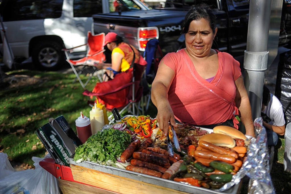 . Maria Campos sells bacon wrapped hotdogs before the USC Trojans vs the Washington State Cougars at the Los Angeles Memorial Coliseum  Saturday, September 7, 2013.  (Photo by Hans Gutknecht/Los Angeles Daily News)