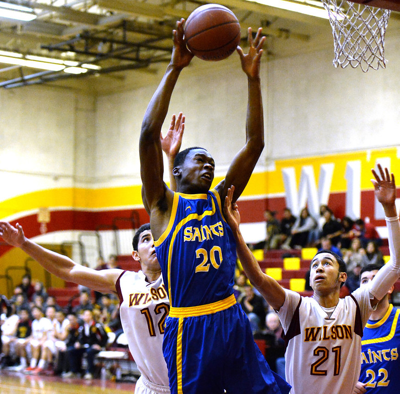 . San Dimas\' Uche Mbaruguru (20) rebounds over Wilson\'s Anthony De Leon (12) and Kevin Price (21) in the first half of a prep basketball game at Wilson High School in Hacienda Heights, Calif., on Friday, Jan. 31, 2014. (Keith Birmingham Pasadena Star-News)
