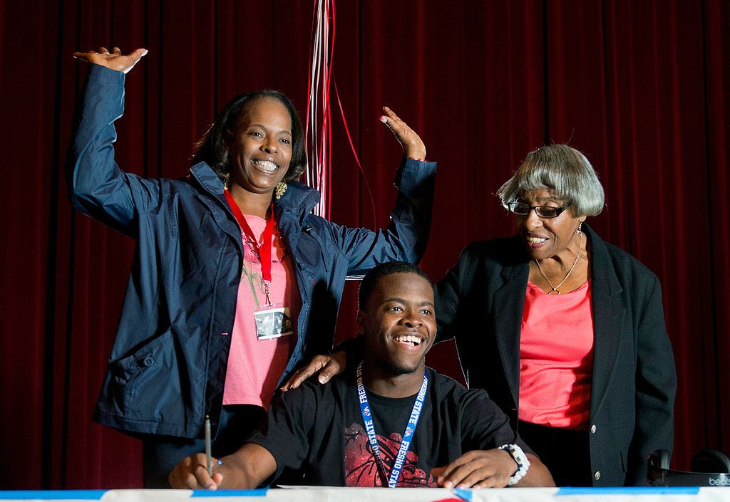 . Monrovia football player DeShawn Potts, 17, signs his national letter of intent to Fresno State during a ceremony with mom, Grenetta Potts, and grandmother, Bertha Reese, at Monrovia High School on Wednesday, Feb. 5, 2014. (Photo by Watchara Phomicinda/ Pasadena Star-News)