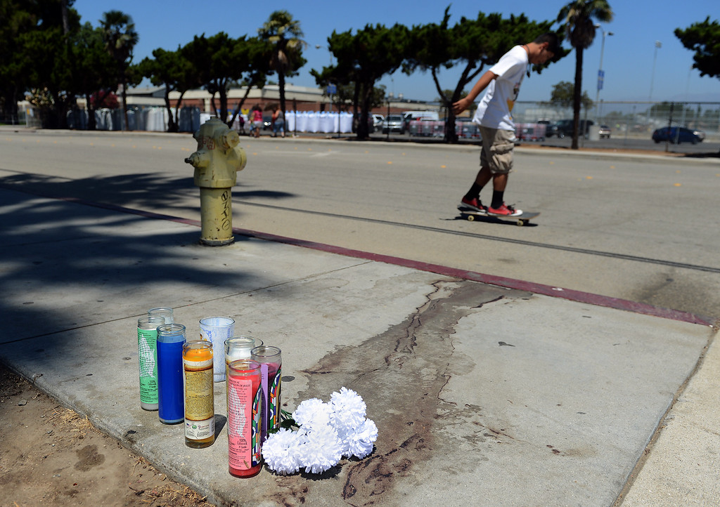 . 0813_NWS_IDB_L-POMHOMICIDES-02-JCM (Jennifer Cappuccio Maher/Staff Photographer) A pedestrian passes by the memorial for Jose Cerda Monday, August 12, 2013, in the 300 block of West Lexington Avenue in Pomona. Cerda, 45, was shot and killed while riding his bike early Saturday evening.