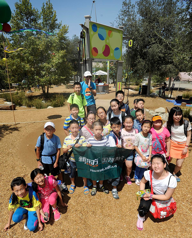 . A group of children visiting from China pose for a group photo. It\'s the one year anniversary of the Galvin Physics Forest at the Kidspace Museum in Pasadena. The museum is commemorating the exhibit\'s one year mark with a three day celebration open to the public.CA. 7/13/2013(John McCoy/LA Daily News)