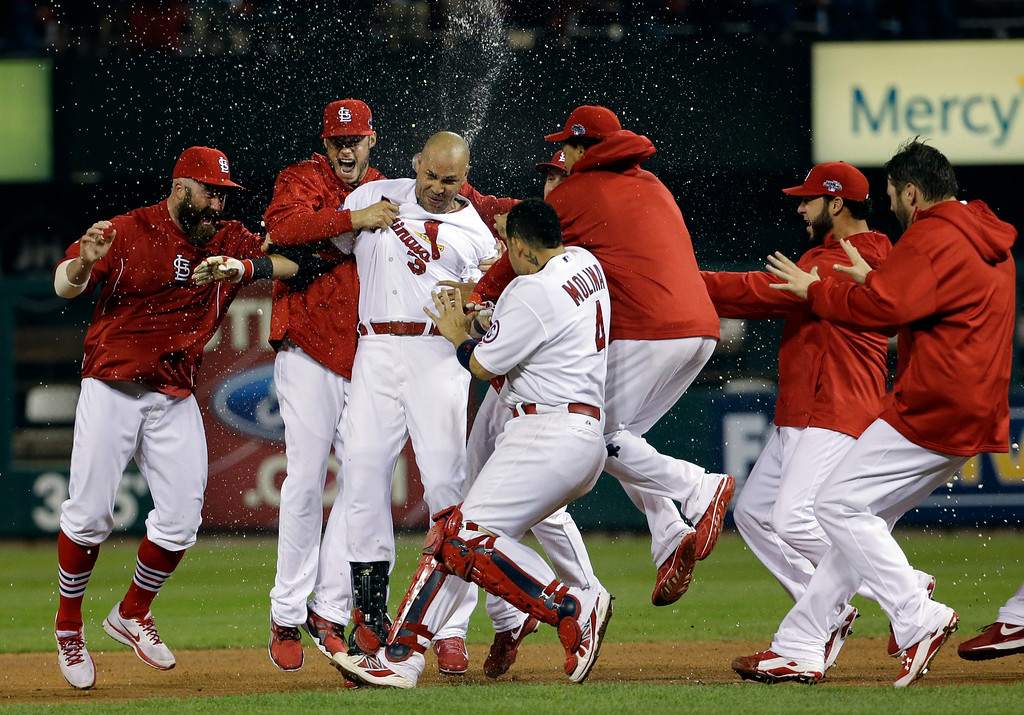 . St. Louis Cardinals\' Carlos Beltran is congratulated by teammates after his game-winning hit during the 13th inning of Game 1 of the National League baseball championship series against the Los Angeles Dodgers Saturday, Oct. 12, 2013, in St. Louis. (AP Photo/David J. Phillip)