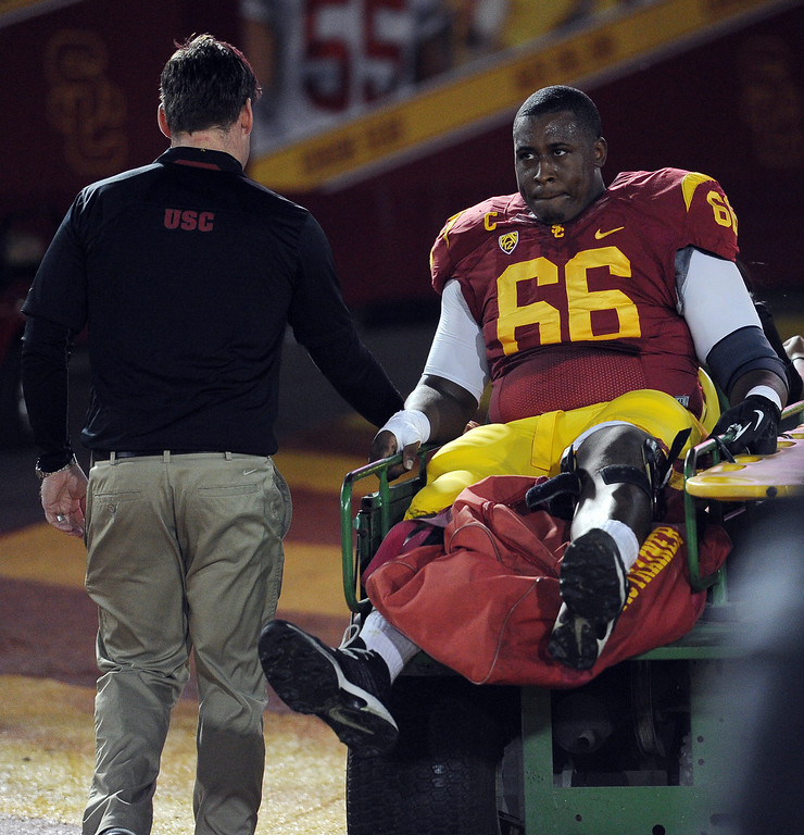 . USC�s Marcus Martin #66 is taken from the field during their game against UCLA at the Los Angeles Memorial Coliseum Saturday, November 30, 2013.  (Photo by Hans Gutknecht/Los Angeles Daily News)