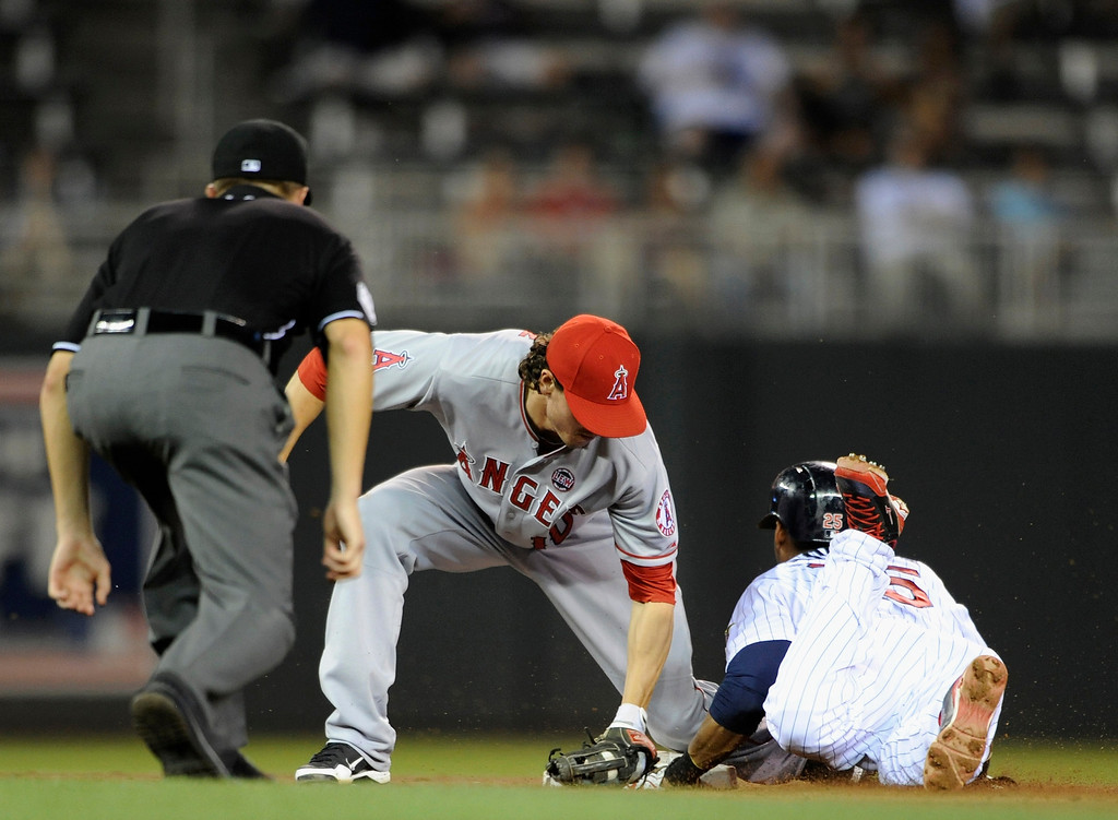 . MINNEAPOLIS, MN - SEPTEMBER 9: Pedro Florimon #25 of the Minnesota Twins steals second base as Grant Green #10 of the Los Angeles Angels of Anaheim applies the tag and umpire Cory Blaser #89 looks on during the sixth inning of the game on September 9, 2013 at Target Field in Minneapolis, Minnesota. The Twins defeated the Angels 6-3. (Photo by Hannah Foslien/Getty Images)