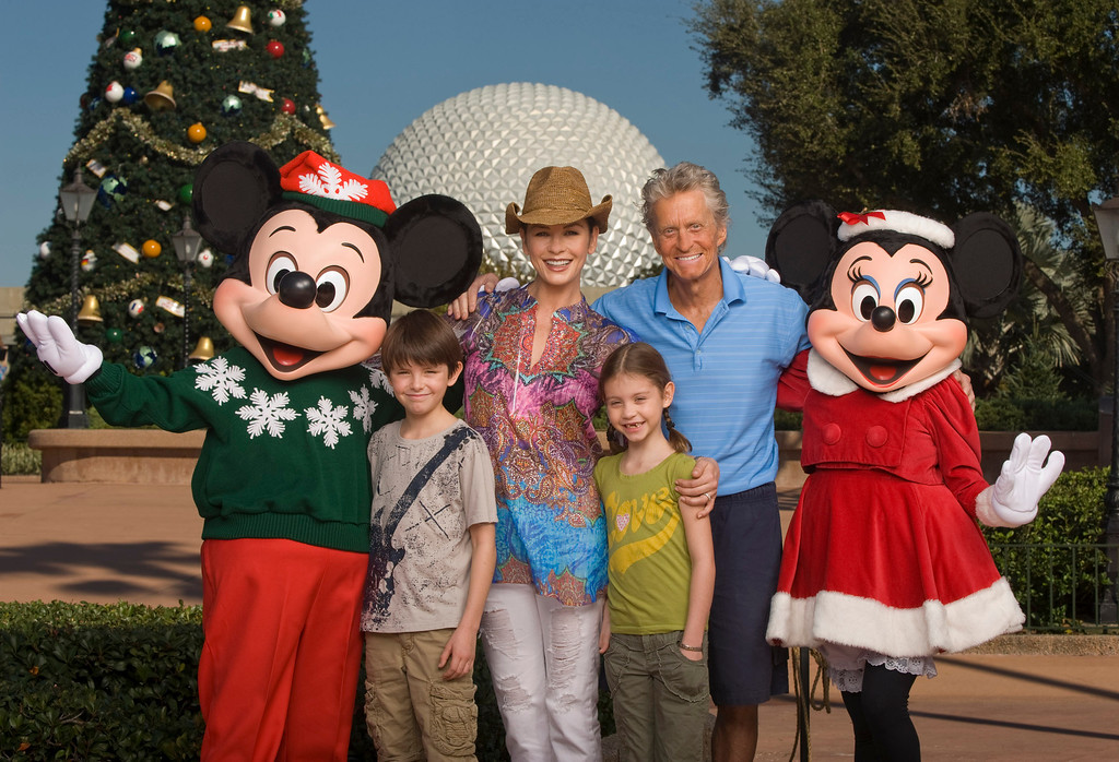 . In this publicity image released by Disney, Mickey Mouse and Minnie Mouse pose with actors Catherine Zeta-Jones and Michael Douglas and their children, Dylan, 10, left, and Carys, 7, in front of the Epcot theme park Christmas tree in Lake Buena Vista, Fla., on Wednesday, Nov. 24, 2010. (AP Photo/Disney, Kent Phillips)