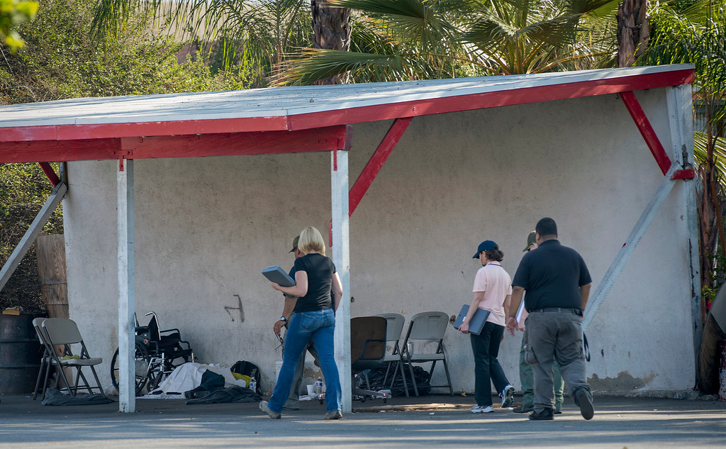 . A crime scene investigators look over a double homicide that left two homeless men stabbed to death at a car wash at Route 66 and Vermont Avenue in Glendora August 15, 2013.  The two men were sleeping overnight at the car wash when the stabbing occurred about 2 a.m.   (SGVN/Staff photo by Leo Jarzomb)