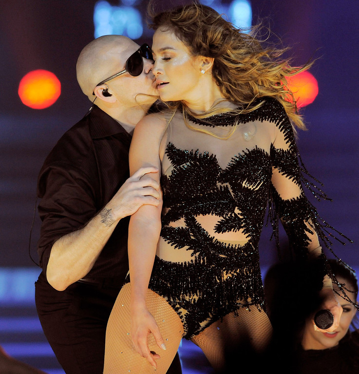 . Jennifer Lopez gets a kiss from guest performer Pitbull during her performance at the Honda Center on Saturday, Aug. 11, 2012 in Anaheim, Calif. (Photo by Chris Pizzello/Invision/AP)