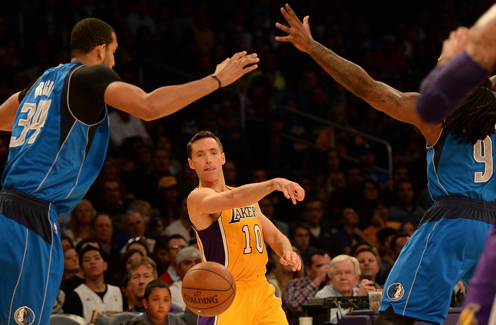 . Los Angeles Lakers guard Steve Nash (10) passes in between the defense of Dallas Mavericks forward Brandan Wright (34) and forward Jae Crowder (9) in the first quarter during an NBA basketball game in Los Angeles, Calif., on Friday, April 4, 2014.  (Keith Birmingham Pasadena Star-News)
