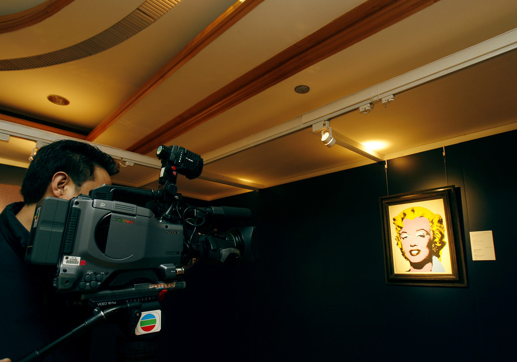 ". A cameraman films a painting by Andy Warhol  entitled ""Lemon Marilyn\""during an auction preview in Hong Kong Wednesday, April 4, 2007. The painting estimated to be worth $15 million will go on sale at auction on May 16 in New York.   (AP Photo/Vincent Yu)"