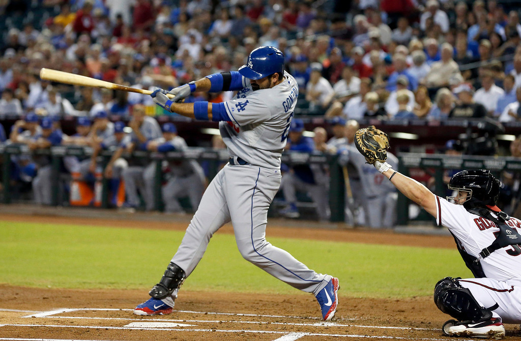 . Los Angeles Dodgers\' Adrian Gonzalez, left, strikes out as Arizona Diamondbacks\' Tuffy Gosewisch catches the ball in the first inning of a baseball game on Monday, Sept. 16, 2013, in Phoenix. (AP Photo/Ross D. Franklin)