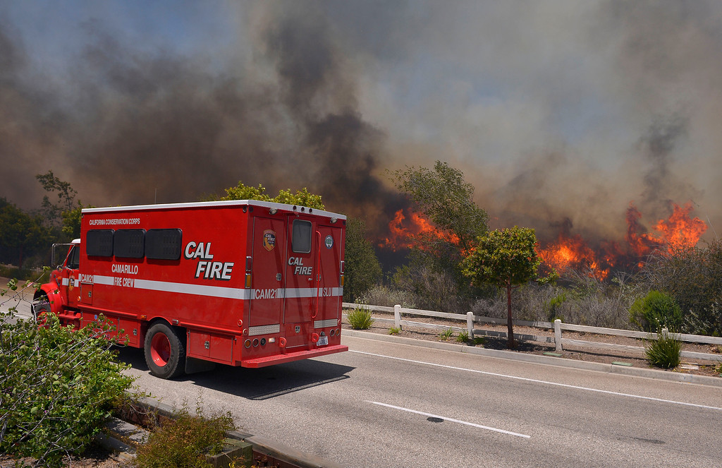 . A fire vehicle stands by as a wildfire burns along a roadside in Thousand Oaks, Calif., Thursday, May 2, 2013. A Ventura County Fire Department spokeswoman said the blaze that broke out Thursday morning near Camarillo and Thousand Oaks, 50 miles west of Los Angeles, had spread to over 6,500 acres, forcing evacuations of nearby neighborhoods. (AP Photo/Mark J. Terrill)