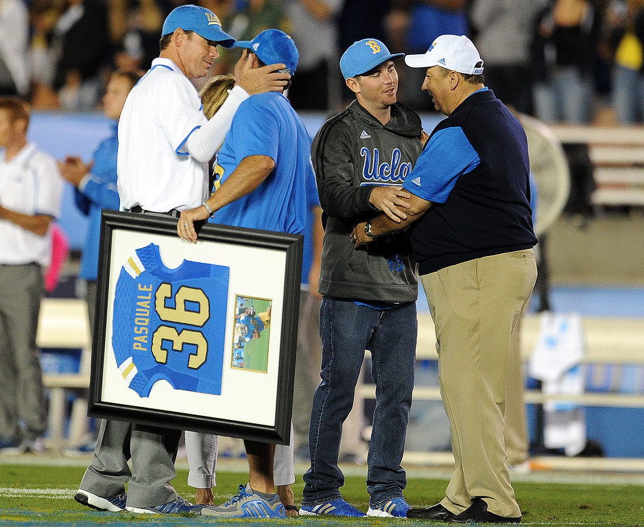 . UCLA head football coach Jim Mora, left, hugs Nicks parents Mel and Laurie Pasquale as Athletic Director Dan Guerrero, right, hugs AJ  during a ceremony between the 1st and 2nd quarter their college football game against New Mexico State in the Rose Bowl in Pasadena, Calif., on Saturday, Sept. 21, 2013. Nick Pasquale, the UCLA receiver was struck and killed by a car on Sept. 8th.   (Keith Birmingham Pasadena Star-News)