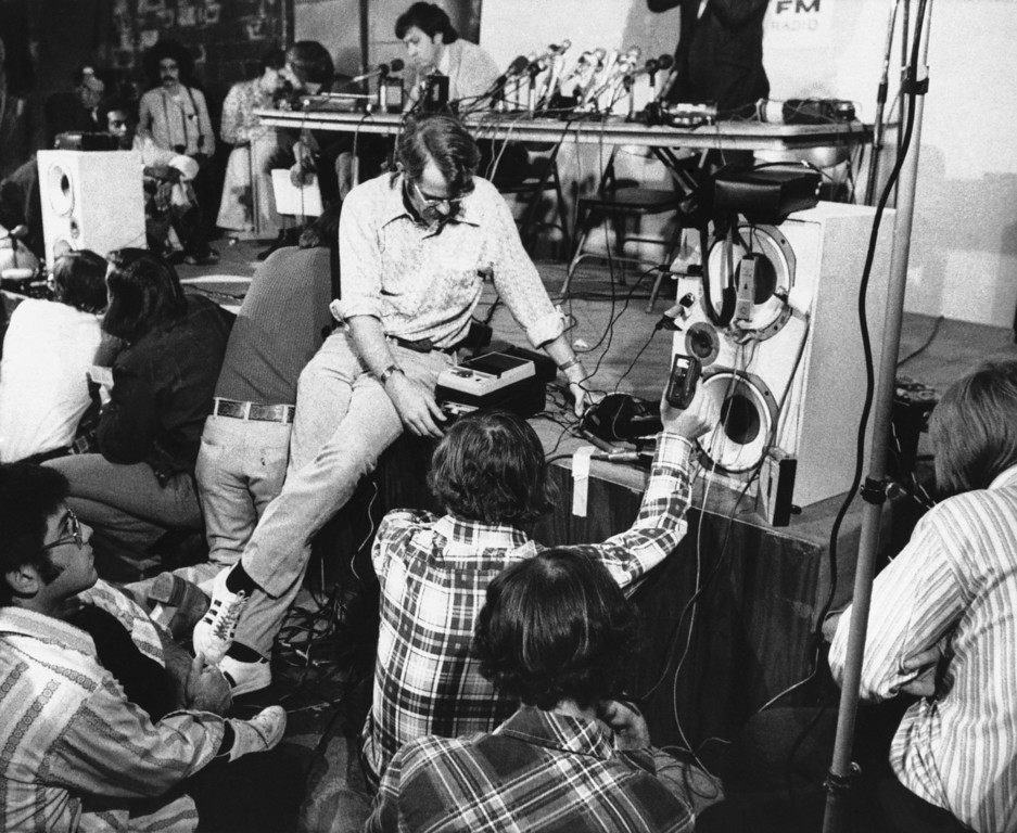 . Newsmen, some holding small recorders, gather around a loud speaker (right center) at radio station KPFK in Los Angeles, June 8, 1974, listening to a new tape made by Patricia Hearst and two companions. The tape, found earlier in the day behind the studio, carried some earthy language as Miss Hearst told of her love for SLA members and defiance of her parents and the establishment. (AP Photo/Wally Fong)