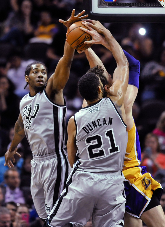 . San Antonio Spurs\' Kawhi Leonard, left, and Tim Duncan defend Los Angeles Lakers center Pau Gasol of Spain during the first half of an NBA basketball game Friday, March 14, 2014. (AP Photo/Bahram Mark Sobhani)