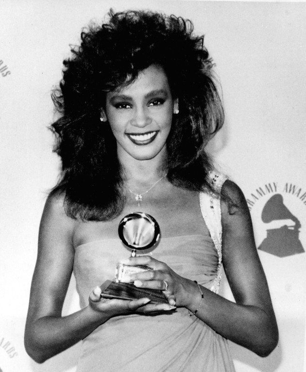""". Whitney Houston poses with her Grammy backstage at the Grammy Awards in Los Angeles, Ca., Feb. 26, 1986.  Houston won best female pop vocal performance for her song \""""Saving All My Love For You.\""""  (AP Photo/Lennox McLendon)"""
