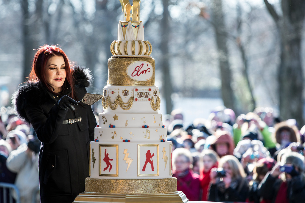 . Priscilla Presley cuts the eight-tiered birthday cake during the 80th birthday celebration for her late ex-husband Elvis Presley at Graceland, Thursday, Jan. 8, 2015, in Memphis, Tenn. A large crowd gathered for the celebration even though the temperature was below 20 degrees. (AP Photo/The Commercial Appeal, Brad Vest)