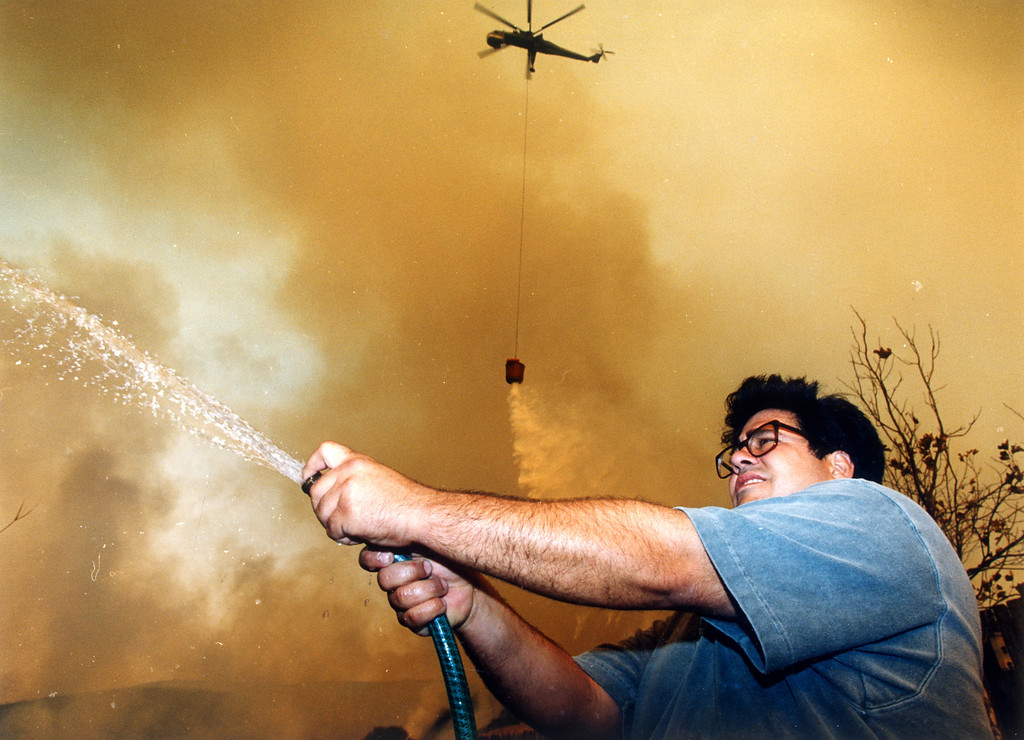 . Tony Perini wets a neighbor\'s roof Wednesday as a helicopter prepares to drop water on the approaching flames off Puerco Canyon Road.  (11/3/93)   Los Angeles Daily News file photo