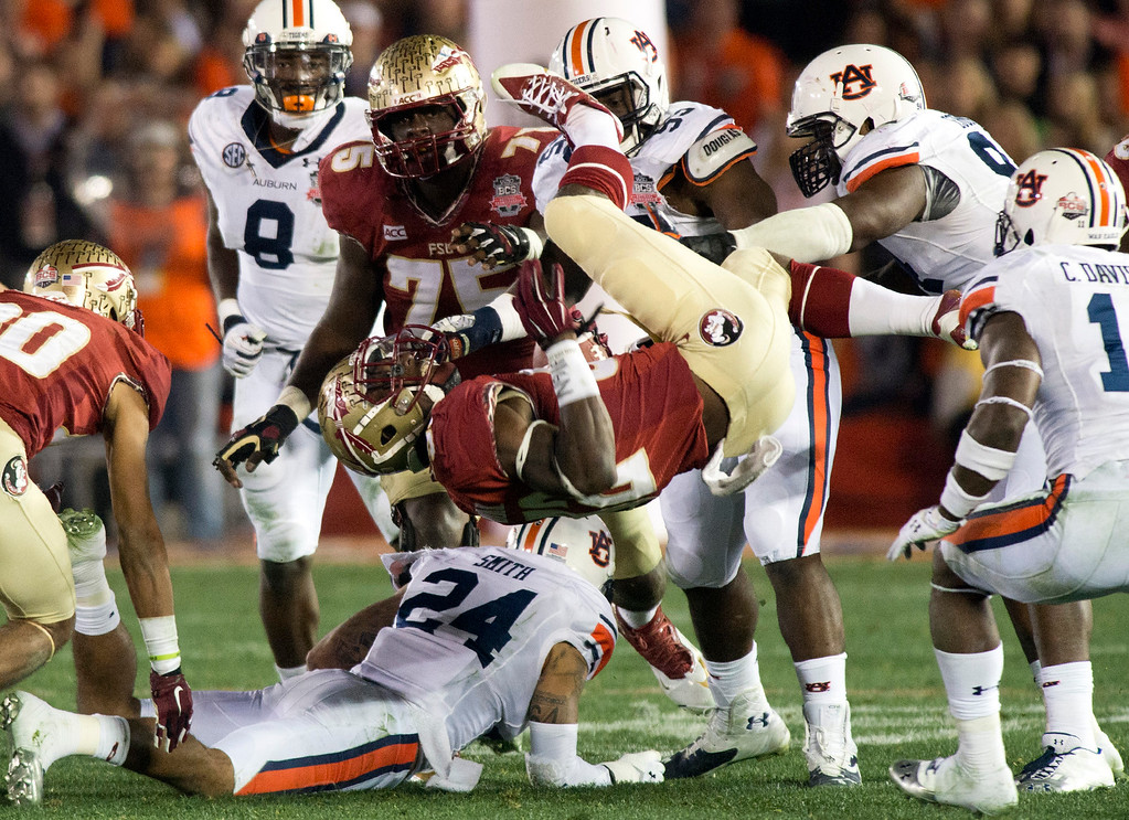 . Florida State\'s running back James Wilder Jr. (32) gets taken down by Auburn\'s defense in the second half during the BCS National Championship game at the Rose Bowl in Pasadena Calif. on Monday, Jan. 6, 2014. (Watchara Phomicinda/ Pasadena Star-News)